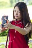 Chica joven en el vestido rojo que toma un selfie Fotografía de archivo libre de regalías
