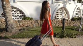 Chica joven en el vestido rojo que viaja en la calle con la maleta almacen de video