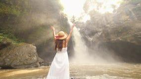 Chica joven en el vestido y Straw Hat Walking a la cascada de Tegenungan y el aumento blancos para arriba de los brazos Viaje des almacen de metraje de vídeo
