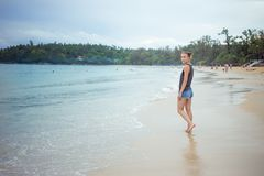Chica joven en fondo azul del mar País tropical Ondas de la playa Puesta del sol amanecer E Foto de archivo libre de regalías