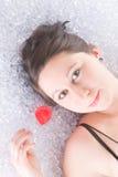 Chica joven en hielo con el pétalo color de rosa Imágenes de archivo libres de regalías