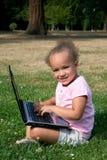 Chica joven en hierba verde con el ordenador portátil fotos de archivo