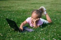 Chica joven en hierba verde con el ordenador portátil Imagen de archivo libre de regalías