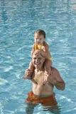 Chica joven en hombros del padre en piscina Imagen de archivo libre de regalías