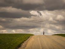 Chica joven en horizonte que camina abajo del camino de campo vacío con las cosechas por ambas partes día nublado Imagenes de archivo
