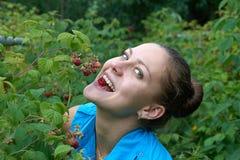 Chica joven en jardín con las frambuesas en la boca Imagen de archivo libre de regalías