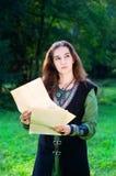 Chica joven en juego medieval con los papeles viejos Fotografía de archivo