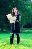 Chica joven en juego medieval con los papeles viejos Imagen de archivo