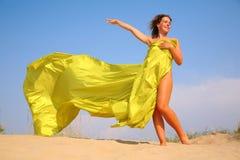 Chica joven en la arena en mantón amarillo de la tela Foto de archivo libre de regalías