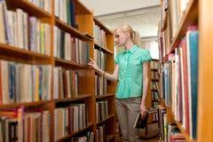 Chica joven en la biblioteca que busca un libro Fotos de archivo libres de regalías