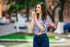 Chica joven en la calle de la ciudad con smartphone y la consumición de la manzana grande Foto de archivo libre de regalías