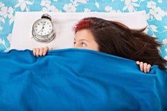 Chica joven en la cama que oculta debajo de su manta del cloc de la alarma Fotografía de archivo