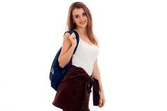 Chica joven en la camisa blanca y con una mochila en hombro que sonríe y que mira la cámara Foto de archivo