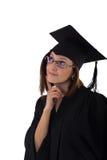 Chica joven en la capa del estudiante que mira soñador Imagenes de archivo