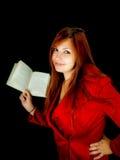 Chica joven en la capa roja que sostiene un libro Foto de archivo