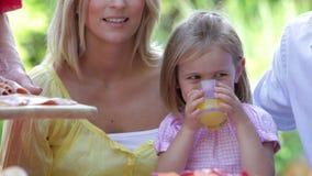 Chica joven en la comida de la familia que bebe el zumo de naranja metrajes