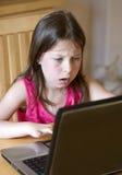 Chica joven en la computadora portátil - cara dada una sacudida eléctrica Foto de archivo libre de regalías