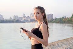 Chica joven en la costa que escucha la música en el teléfono móvil Imagen de archivo