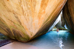 Chica joven en la cueva en la playa tropical Foto de archivo libre de regalías