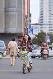 Chica joven en la e-bici en el centro de ciudad, Kunming, China Fotos de archivo libres de regalías