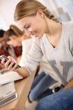 Chica joven en la escuela usando smartphone Fotos de archivo libres de regalías
