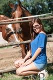 Chica joven en la granja rodeada por los caballos Fotografía de archivo