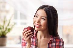 Chica joven en la manzana sana de la tenencia de la situación de la forma de vida de la cocina que mira hacia fuera el primer ale foto de archivo libre de regalías