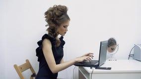 Chica joven en la oficina, administrador de oficinas, sentándose en el ordenador portátil, texto que mecanografía, mirando a v almacen de metraje de vídeo