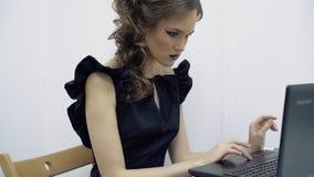 Chica joven en la oficina, sentándose en el ordenador portátil, texto que mecanografía, mirando a veces el teléfono almacen de video
