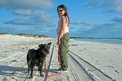 Chica joven en la playa con el perro foto de archivo libre de regalías