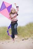 Chica joven en la playa con la sonrisa de la cometa Imágenes de archivo libres de regalías