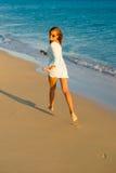Chica joven en la playa en la puesta del sol Foto de archivo libre de regalías
