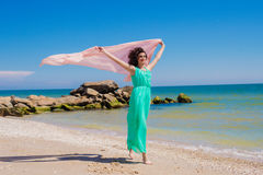 Chica joven en la playa en verano con una bufanda del vuelo Foto de archivo libre de regalías
