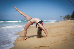 Chica joven en la playa que hace excercises de la mañana Foto de archivo