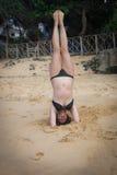 Chica joven en la playa que hace excercises de la mañana Imagenes de archivo