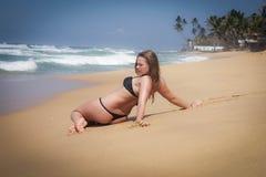 Chica joven en la playa que hace excercises de la mañana Imágenes de archivo libres de regalías