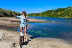 Chica joven en la playa que juega con un perro Fotografía de archivo libre de regalías