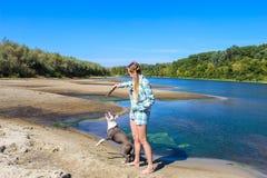 Chica joven en la playa que juega con un perro Foto de archivo