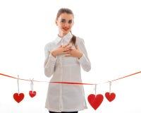 Chica joven en la ropa blanca que coloca cintas cercanas con los corazones Imágenes de archivo libres de regalías
