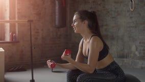 Chica joven en la ropa de deportes negra que hace ejercicio con pesas de gimnasia rojas en el fondo de una pared de ladrillo almacen de video