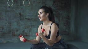Chica joven en la ropa de deportes roja que hace ejercicio con pesas de gimnasia en el fondo de una pared de ladrillo almacen de metraje de vídeo