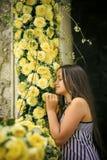 Chica joven en la rosa amarilla del olor del vestido del verano, primavera fotografía de archivo