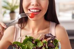 Chica joven en la situación sana de la forma de vida de la cocina con el cuenco que come el primer feliz de la cara de la ensalad fotos de archivo