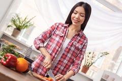 Chica joven en la situación sana de la forma de vida de la cocina que corta las verduras que cocinan la sonrisa alegre fotos de archivo libres de regalías