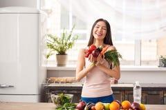 Chica joven en la situación sana de la forma de vida de la cocina que lleva a cabo la risa de las verduras alegre imagen de archivo
