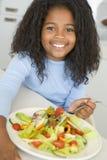 Chica joven en la sonrisa de la ensalada de la consumición de la cocina Fotografía de archivo