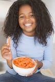 Chica joven en la sonrisa de los palillos de zanahoria de la consumición de la cocina Foto de archivo