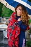 Chica joven en la terraza debajo de un paraguas, vidrios que llevan con el pelo largo Esperas, trastorno El concepto de emoción Foto de archivo libre de regalías