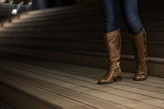 Chica joven en las botas de cuero que camina abajo de las escaleras imagen de archivo
