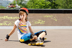 Chica joven en las cuchillas del rodillo que sientan la observación Imagen de archivo libre de regalías
